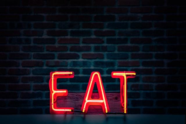 červený nápis eat v černé tmě na zděné zdi z cihel