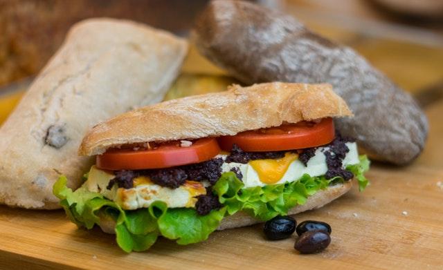 rohlík plněný sýrem, rajčetem, salátem, za ním další dva kousky pečiva